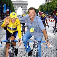 Cyclist Lance Armstrong rides alongside team manager, Johan Bruyneel