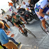Jon Tiernan-Locke in the green jersey of leader of the Haut Var race, cycling up a very steep hill cheered on by crowds