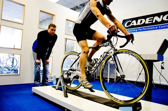 A cyclist pedals on a turbo trainer while a coach watches