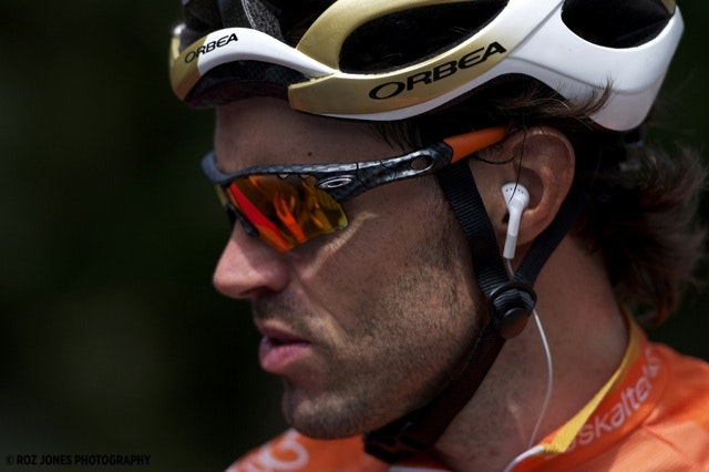 Cyclist, Sameul Sanchez, wearing a white and gold helmet, Oakley sunglasses, and an orange jersey