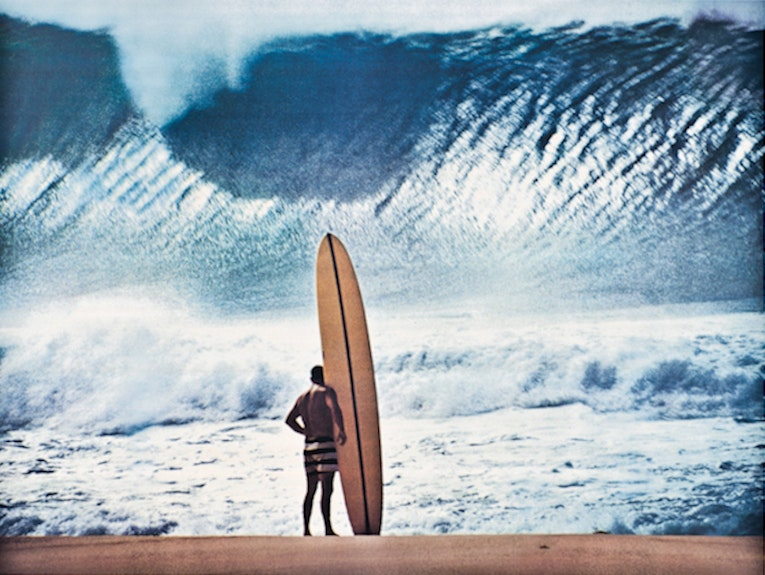Greg Noll in his signature striped board shorts at Pipe, by John Severson